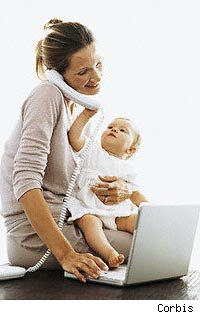 Mother on phone and laptop with baby on her lap