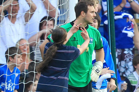 Schoolgirl joins football pitch invasion and gives the goal keeper two fingers