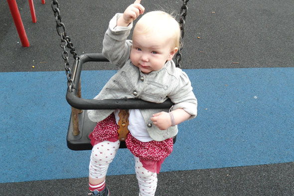 Baby Diana in a playground swing