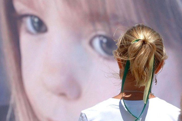 Madeleine McCann's mother Kate McCann looks at a poster of her daughter