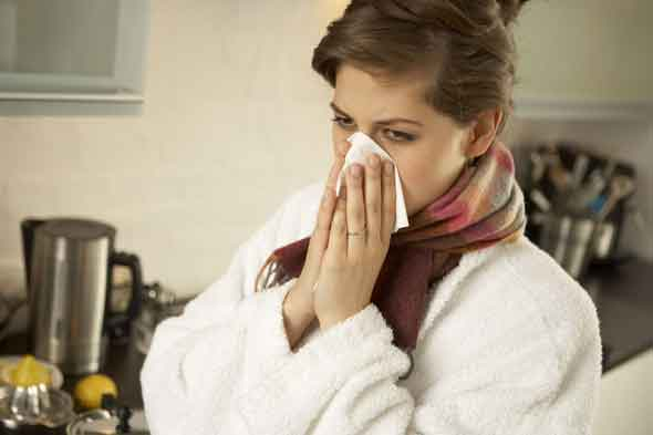 Woman with a cold wiping nose