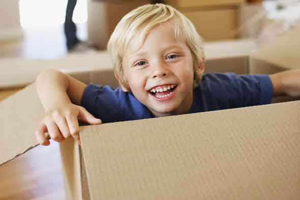 Young child playing with a cardboard box