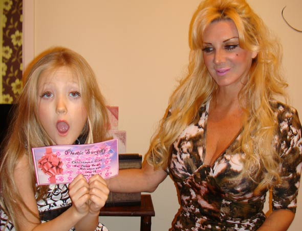 Poppy Burge with her liposuction voucher from 'Human Barbie' mum Sarah Burge