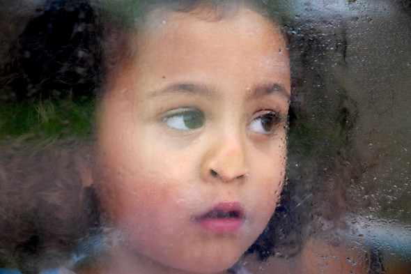 Child looking out of a window on a rainy day