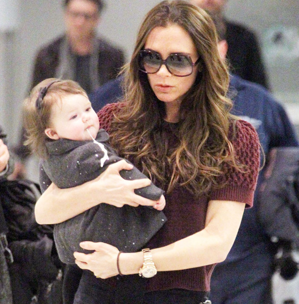 Baby Harper is sick on herself and mum Victoria in crowded airport