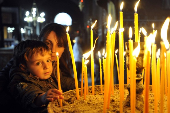 Mother and child lighting candles at church