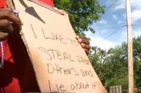 Parents make daughter wear sign admitting she stole