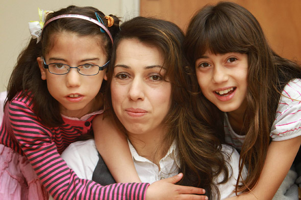 One of my twin daughters will never smile: Ines who has Moebius Syndrome with her mother and twin Imen