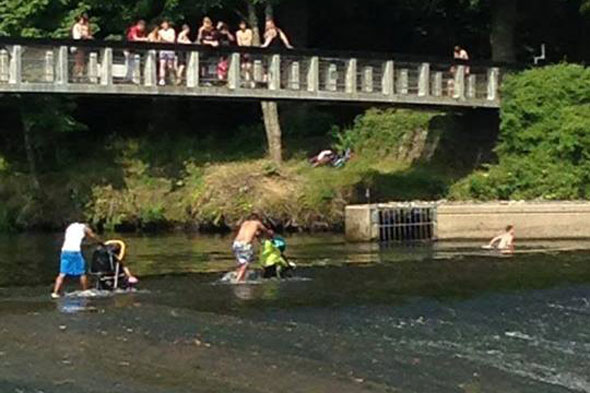 Daft dads push kids in buggies across dangerous river