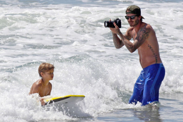 Surf's up! Dashing dad David Beckham hits the beach with Brooklyn, Romeo and Cruz