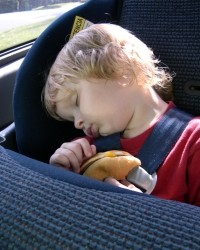 A child sleeping in his carseat while holding the remains of his hamburger.