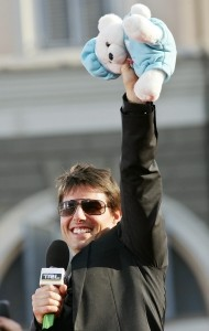 Tom Cruise holding a teddy bear up in the air