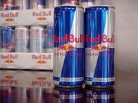 Two cans of Red Bull with 24-can tray as background