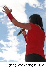 A women singing with a blue sky and clouds in the background