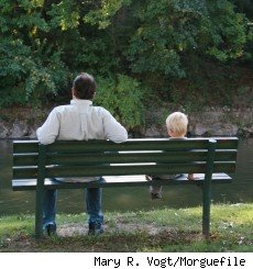 A dad and his son sitting on a bench by a pond