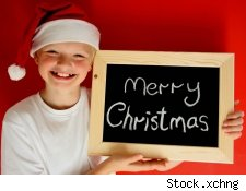 A boy wearing a santa hat holding a chalkboard that says