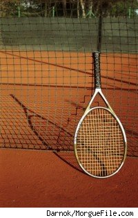 A Tennis racket leaning up against a net.