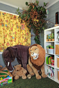 child's playroom with stuffed animals and a tree
