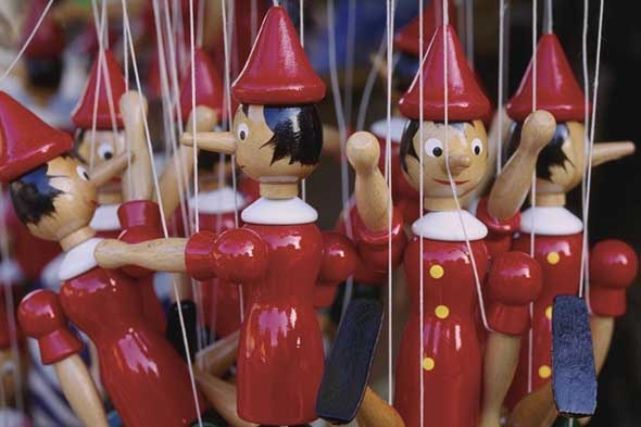 Toy Pinocchio puppets lying teenagers