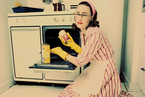 retro housewife cleaning oven
