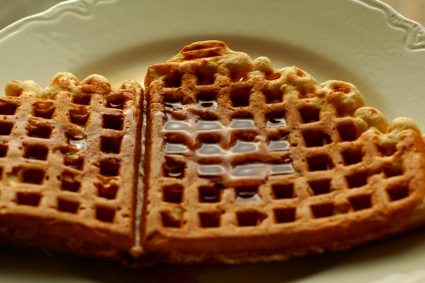 half a waffle, drizzled with maple syrup, on a white plate