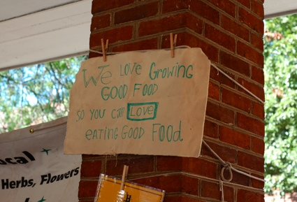 photo of sign at farmers market that says we love growing good food so you can love eating good food.
