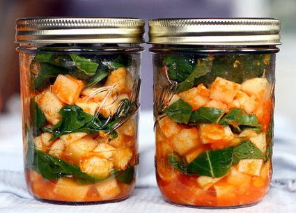 two wide mouth pint jars of daikon radish kimchi