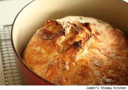 a pot with a baked loaf of no-knead bread 