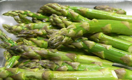 a pan of raw asparagus ready for roasting