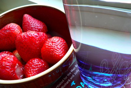 a bowl of strawberries and a glass of water