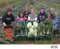 UCSC students posing with an assortment of local, organic produce