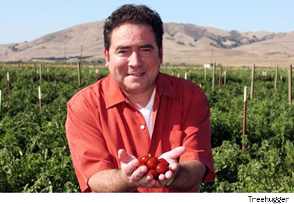 Emeril Lagasse holding a handful of tomatoes