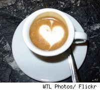 A cup of cappucino witht the foam forming a heart.