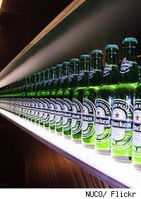 Bottles of Heineken lined up on a bar.