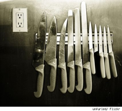 A set of knives attached to a magnetic strip on a wall.