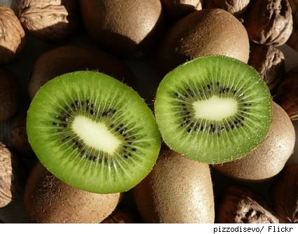 Artsy image of a kiwi cut in half to show the inside, in front of other uncut kiwis.