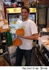 Maximillian Shrem proudly holds two halves of Mimolette cheese.