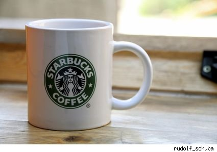 White coffee mug with green Starbuck's label on it.