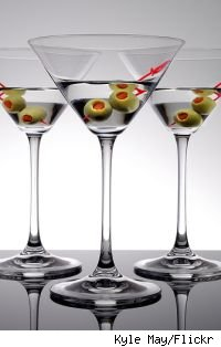 Three martini glasses with vodka and olives in each.