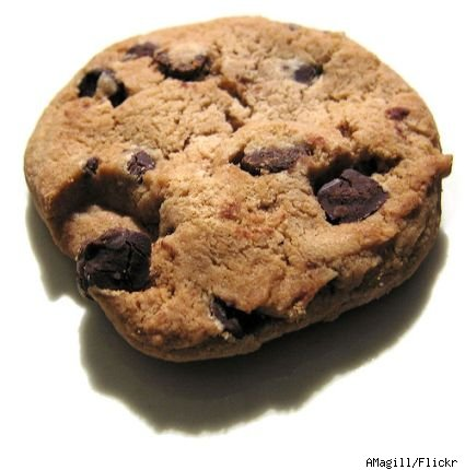 Close up view of a chocolate chip cookie on a white background.