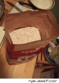 An open bag of flour on a countertop seen from above.