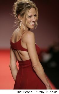 Sheryl Crow in a red dress, looking back over her shoulder.