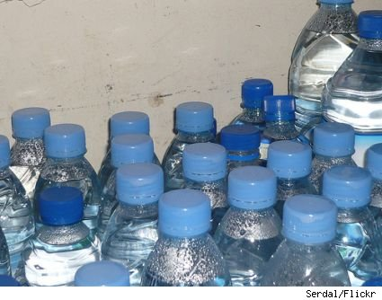 A collection of water bottles, viewed from halfway up, all with blue caps.