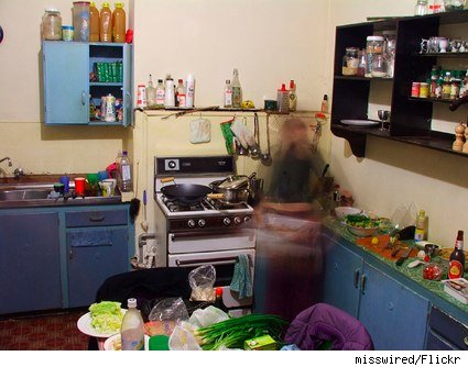 image of a blurry woman cooking in a blue kitchen