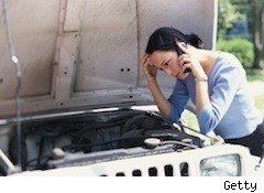 woman bending over car engine calling for help