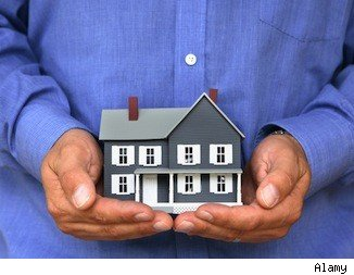 Mortgage insurance: hands holding a home.